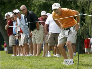 Jim Searles of Fostoria, right, and other spectators watch a shot by golfer Nick Price on #17.