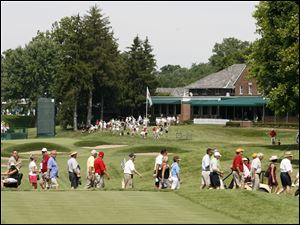 Spectators cross a path on the fairway of the 18th hole.