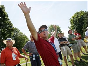 Steve Essig, of Holland, Ohio, signals for the gallery to remain quiet and still around the 18th tee.