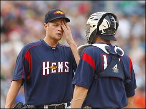 Mud Hens pitcher Andy Oliver speaks with catcher Max St. Pierre during the fourth inning.