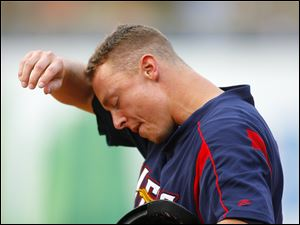 Mud Hens player Brandon Inge wipes the sweat from his brow after reaching first base against the Norfolk Tide.