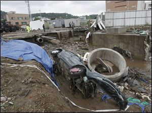 A wrecked car is left in mud Thursday after it was washed away by heavy rain in Seoul, South Korea.