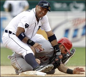 Detroit Tigers second baseman Carlos Guillen lands on Los Angeles Angels' Jeff Mathis at second base after throwing to first base on a Erick Aybar fielder's choice in the seventh inning Thursday.