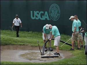 The ground crew suctions water from one of the bunkers on the 18th hole Friday at Inverness.