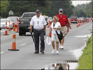 Toledoans, from left, Hall Dement, Diana Ries, and Mike Godwin dodge puddles as they walk along Dorr Street to the golf course.