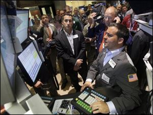 Traders gather on the floor of the New York Stock Exchange, where jitters over a possible U.S. default and a bad economy were evident.