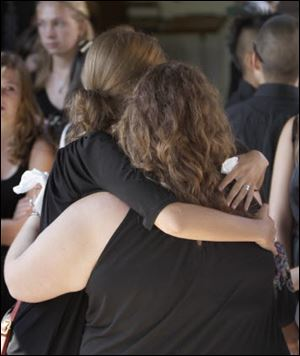 Two women embrace in Barling, Ark., Saturday after a service for four of the five victims of a shooting rampage last weekend at a Grand Prairie, Texas roller rink.