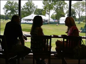 In silhouette, Rick and Debbie Martin, left, enjoy their view of the 18th green with Beth Miller in the Health Care REIT suite.