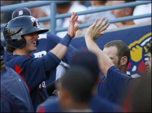 Hens player Will Rhymes is congratulated in the dugout after scoring in the first inning.