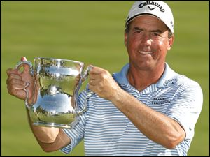 Olin Browne poses with the Francis D. Ouimette Memorial Trophy after winning the 2011 U.S. Senior Open at Inverness Club. Browne finished 15 under par