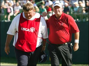 Mark Calvecchia, right, leaves the 18th green with his caddie, Eric Bajas, left, after finishing the fourth round. Calcaveccia finished third in the tournament.