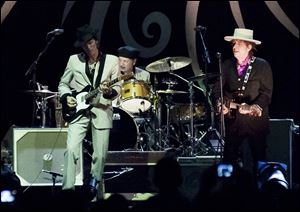 Bob Dylan , right,  performs with his band, including guitarist Charlie Sexton, left, at a concert in Vietnam this past April.