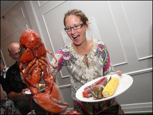 Candy Millon lifts a whole steamed lobster at the Toledo County Clubs annual lobster party.