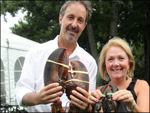 Hosts Trey and Kim Brunsting hold lobsters with their claws banded closed.