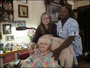 Mary Jackson, 80, seated with her daughter Pam Feichter, standing at left, and caretaker Shantoya Lyons, has lived with her adult daughter and son-in-law Bob since Ms. Jackson's heart attack several years ago. Ms. Lyons, an STNA with Comfort Keepers, works at the family home 25 hours a week through the PASSPORT program.