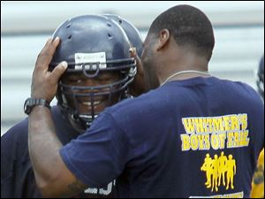 Tight end coach Wondell Hill congratulates a player after a good play.