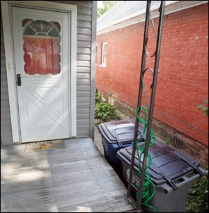 The Decosters put the two city-issued receptacles against the porch of their East Toledo home, with the wheels toward the curb, to make taking out the trash easier. The city has no requirements on can placement.