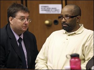 Defense attorney John Parker, left, talks with Anthony Sowell during court proceedings July 19.