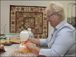 Rita Thomas, a Sylvania resident and quilter who will be making the trip to Joplin this month, stitches quilt pieces together at the group's workshop.