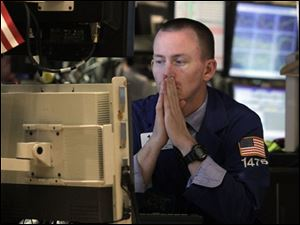 Specialist James Ahrens works at his post on the floor of the New York Stock Exchange Wednesday. Wall Street focused on the bleak landscape ahead for the economy and sold off, wiping out the big gains from a day earlier and then some.
