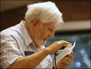 Paul Rachow, one of the six organizers of the support group in 2005, uses a magnifier to study his notes for the meeting at the Holland branch library.