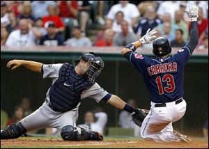 Cleveland Indians' Asdrubal Cabrera slides safely into home ahead of the tag by Detroit Tigers catcher Alex Avila on a sacrifice fly by teammate Carlos Santana Tuesday  night.