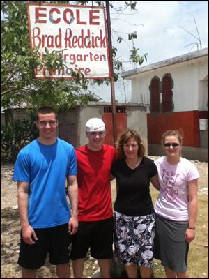Debbie Reddick, second from right, a Perrysburg Schools employee, joined John, Jim, and Grace, the three youngest of her eight children, recently outside the K-6 school in Savanette, Haiti, that is named for Ms. Reddick's late husband.