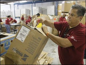 Hickory Farms CEO Mark Rodriguez breaks down a box as other Hickory Farms employees pack food boxes at the Toledo Nor