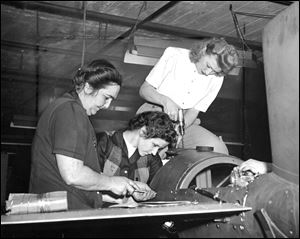 1945: Angela Durieux, Rossford, sits astride one of the robombs produced at the Willys-Overland Motors Inc. plant in Toledo, while Viva Hatt, Lottie Myskinski, and Agnes Mack (hands at right) of Toledo, work on assembling this war weapon.