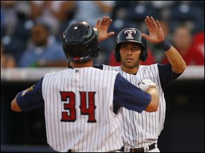 Hens player Clete Thomas (34) is met at the plate by teammate Ben Guez after hitting a home run.