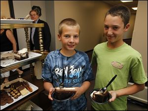 Brothers Danny, left, and Matt Wainstein, of Toledo, get dessert outside the Rudolph/Libbe suite.