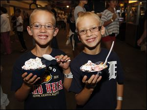 Jack Tanner, left, and Jordan Judkins, both of Adrian, Mich., eat ice cream out of batter helmets.