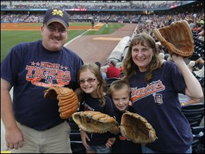 The Johncox family, from left, Justin, Mackenzie, Hunter and Kellie, bring their gloves to Fifth Third Field.