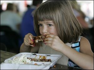 Maumee resident Allison Launder, 6, enjoys some ribs during the event.