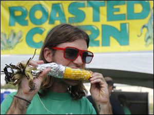 Indiana resident Will Staler eats roasted corn during the rib-off.