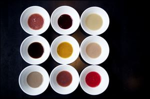A variety of ketchups at Jose Andres' restaurant, America Eats Tavern. Left to right top row, blueberry, blackberry, oyster; left to right middle row, mushroom, yellow tomato, gooseberry; left to right bottom row, anchovies, spice berry and red currant.