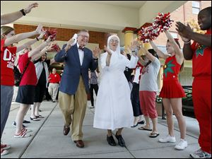 Mr. Gee and Mother Cecilia dance through a tunnel of students and cheerleaders at the