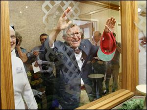 Mr. Gee waves to OSU mascot Brutus Buckeye through a window at the Sacred Heart Home for the Aged.