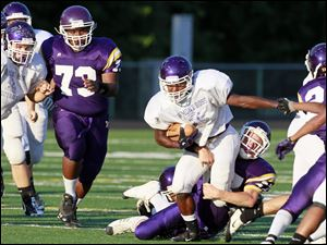 Fremont Ross running back Jabree Lather (27) is brought down by Waite's Kenny Hade (27).