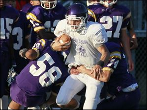Fremont Ross QB Tyler Wolf (12) is brought down by Waite's Nicholas Jensen (58) and Jeremy Zervas (74).