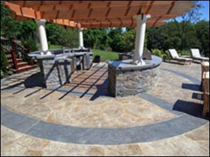 Concrete patios, like this one by New England Hardscapes Inc., can turn your backyard into a beautiful sanctuary.