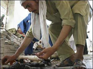 Pakistani villagers collect ball bearings after a suicide bombing at a mosque in Pakistani tribal area of Ghundi Friday.
