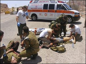 Wounded Israeli soldiers are treated at the site of a shooting attack. Gunmen crossed into Israel from neighboring Egypt Thursday and set up an ambush, the military says.