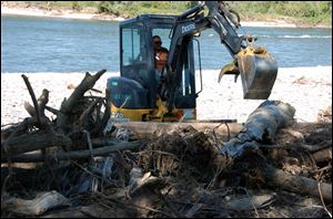 associated pressAn excavator pulls apart a debris pile along a stretch of the Yellowstone River near Billings, Mont. Oil contaminated the river when a pipeline burst in July.