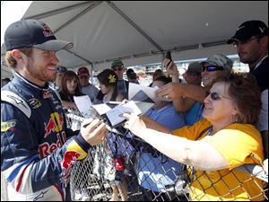 NASCAR driver Brian Vickers gives fans a smile while signing autographs at Michigan International Speedway.