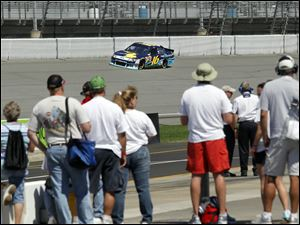 Fans watch as NASCAR driver Greg Biffle takes a practice lap for the Pure Michigan 400.