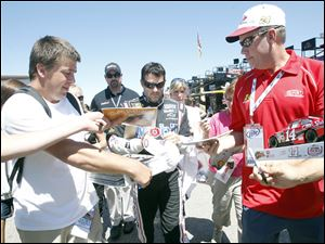 NASCAR driver Tony Stewart is surrounded by fans while walking through the pits.