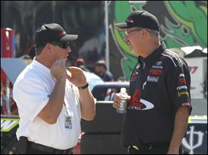 Terry Cook, competition director for Red Horse Racing and former Late Model track champion at Toledo, Sandusky and Flat Rock speedways, left, speaks with Butch Hylton, Timothy Peters crew chief, right, at Michigan International Speedway.