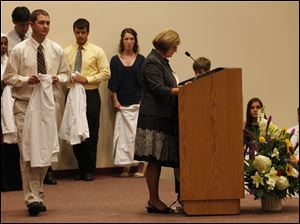 Jacob Eby of Sylvania walks on stage to have his white coat put on him during the ceremony.