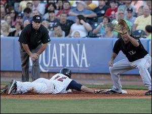 Mud Hens player Jeff Salazar slides back to base before the ball hits the glove of the Lousiville first baseman.